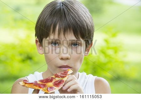 Appetite Boy eating pizza on  the nature