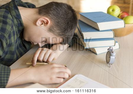 Tired Schoolboy Asleep On A Desk While Doing Homework At Home