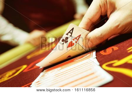 Hand with ace poker cards on table. Success casino concept