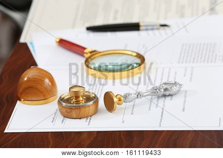 Documents, wooden ink pad, stamps and magnifier on notary public table