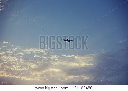 Passenger airplane in blue cloudy sky long away