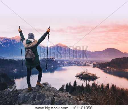 Travel Slovenia Europe. Woman looking on Bled Lake with Island Castle and Alps Mountain on background. Top view. Bled Lake one of most amazing tourist attractions. Sunset winter nature landscape.