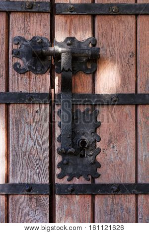 Closeup of an ornamental iron hinge on old wooden door