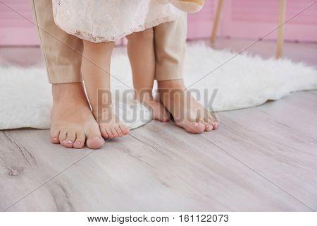 Mother and daughter legs on wooden floor indoors
