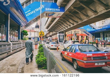 Kuala Lumpur, Malaysia - February 7, 2016: Unidentified people in traditional clothes on the background of the urban landscape in the city centre Jalan Tun Perak, Kuala Lumpur, Malaysia.