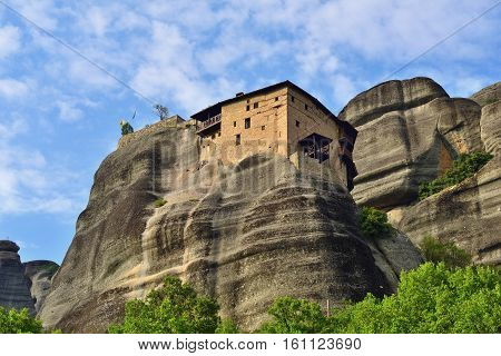 Meteora monasteries. Bottom view on the Holy Monastery of St Nikolaos Anapafsas placed on the edge of high rock at sunset light Kastraki Greece