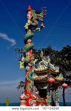 Hua Hin Thailand - December 29 2009: Dragon with its long tail wrapped around a red pole at the Tewapitak Pok Pak Rom Yen Chinese temple