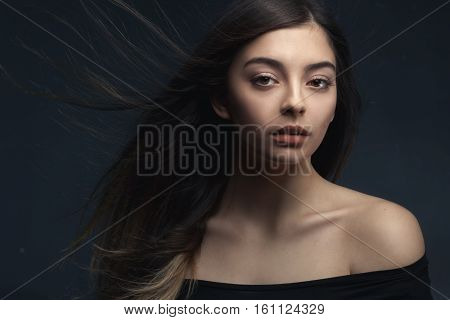 closeup studio portrait of attractive young woman with long brown hair over dark studio background