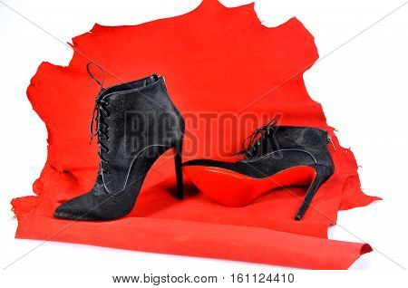 Ukraine Kiev - August 25 2016: Women's black ankle boots handmade on a piece of material from the red skin. Imitation brand shoes Christian Louboutin showing red soles - illustrative editorial