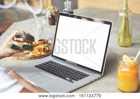 Rear View Of Student Sitting In Front Of Open Generic Laptop With Burger In His Hand, Working On His