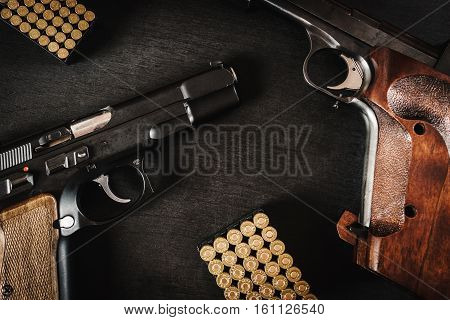black pistols and bullets on a black wooden table