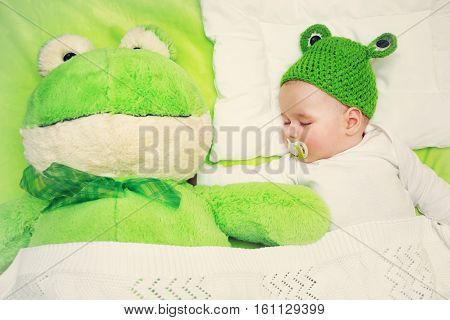 little boy in knitted animal hat sleeping on soft green blanket with frog soft toy. Cute 5 month old baby on the pillow in bed