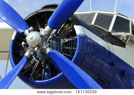 Propeller of plane engine, vintage passenger biplane with fuselage of blue and white colors, retro aircraft, civil aviation, ready to start, blue sky on background