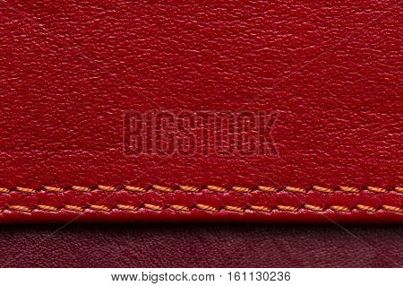 Leather samples with stitches, natural materials of red and maroon colors, seams with orange thread, woman bag detail, macro shot, abstract background