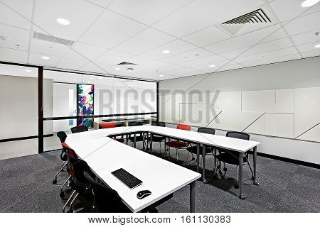 Modern conference room with round white table and chairs next to glass door