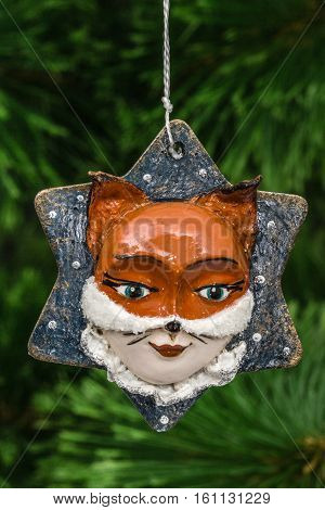 Festive decoration in the shape of a foxy mask on a Christmas tree background