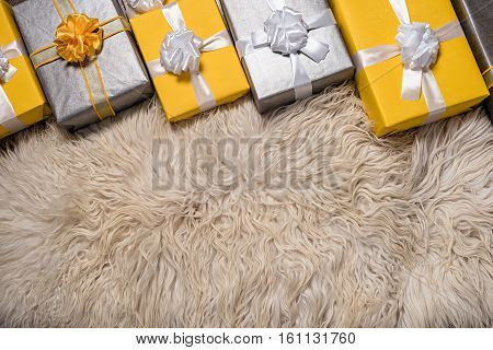 A pile of yellow and gre Christmas gifts in colorful wrapping with ribbons against the wall on a beautiful hardwood floor with copyspace poster