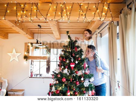 Young father giving his little daughter piggyback decorating Christmas tree together.