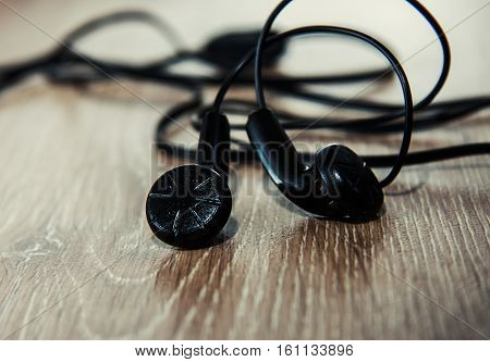 small black earphones in a wooden background