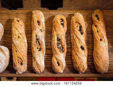 closeup of some baguettes or bread rolls on a wooden table in bakery. Fresh baguettes with olive