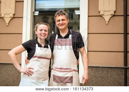 two happy bakers stand near the bakery