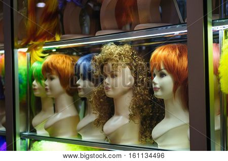 Mannequins in a shop window with colored hair.