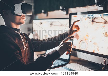 Experiencing virtual reality. Handsome young man wearing virtual reality headset and gesturing while sitting at his desk in creative office