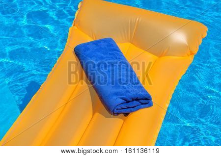 Blue towel on an orange inflatable mattress floating in the poo