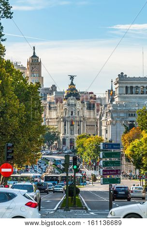 View from Plaza de la Independenci, Madrid, to Metropolis building.  Busy, mid-day street scene.  Spain urban life, traffic & cars in foreground.