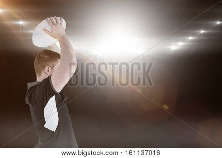 3D Rugby player about to throw a rugby ball against spotlight
