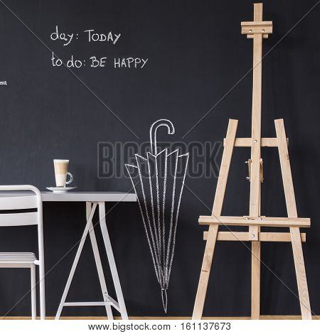 Desk And Easel Against Blackboard Wall