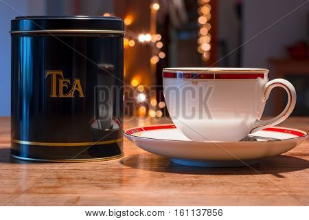 White china cup of tea and black tea tin on the wooden table.