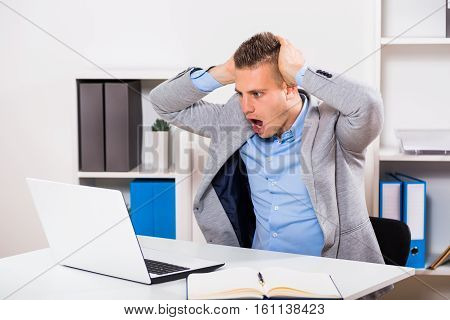 Businessman sitting at the table and looking at his laptop in panic.