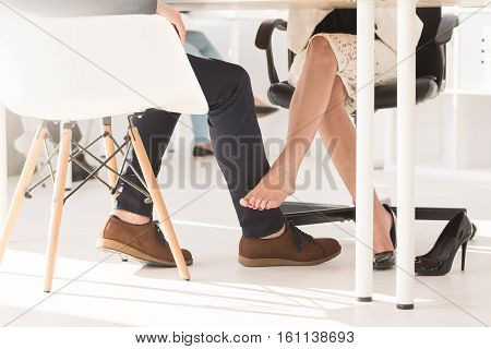 Couple Touching Each Other Under The Table