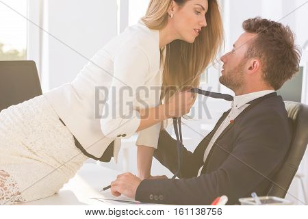 Woman  Holding Man's Tie In The Office