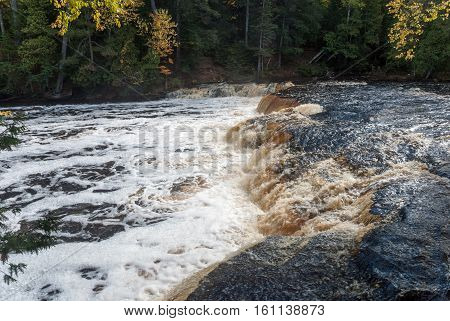 Brown-black waters of the Lower Falls on Tahquamenon River, Tahquamenon Falls State Park, Chippewa County, Michigan, USA