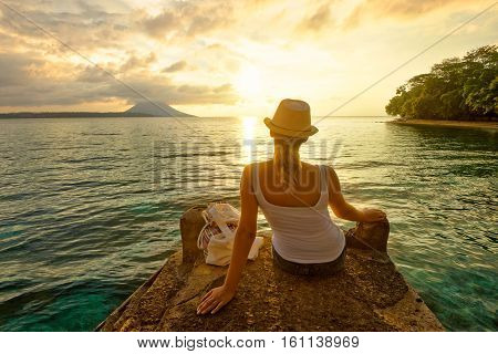 Rear view of a romantic young woman backpacker sitting on the pier enjoying stunning sunset