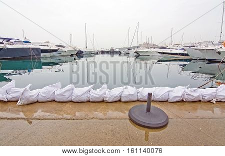 IBIZA BALEARIC ISLANDS SPAIN - OCTOBER 25 2016: Sand bags on low level jetty after storms and rain on an overcast day on October 25 2016 in Marina Botafoch Ibiza Balearic islands Spain.