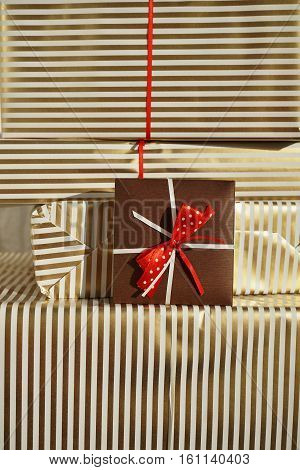 Side view of heap of gifts (presents) wrapped in lined wrapping paper with white and golden lines with a small brown parcel beside them as a symbol of giving and receiving presents