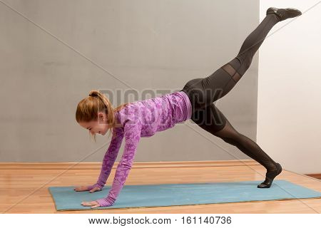 Young slim caucasian woman working out doing plank with one leg up.