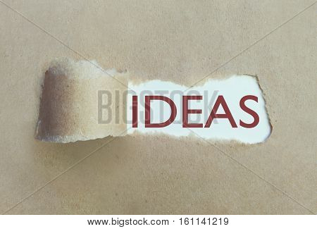 Torn brown paper uncovering the word ideas