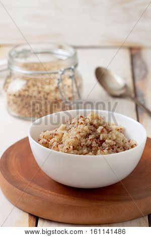Dietary healthy breakfast. Cooked quinoa in a white bowl quinoa in a glass jar on a wooden background