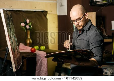 Artist draws a still life, holding a brush and palette. Apples and vase with flowers on background. In workroom