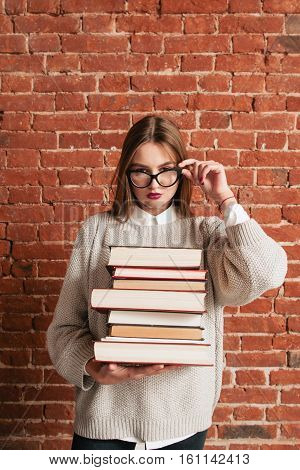 Sexy student with books looking through glasses. Attractive young woman posing with bunch of tutorials, free space on brick wall background. Challenge, sex, seduction, education, hard exam concept