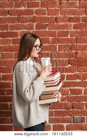 Profile of student going with books and coffee. Young woman walking to college with literature and coffee-to-go, free space. Modern life, urban, coffee break, education concept