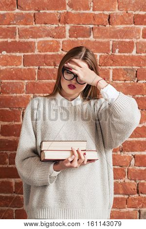 Stressed girl with books forgot something important. Desparate woman girl covering her face with hand. Stress, education, bad memory, tiredness concept