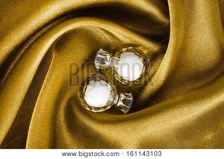 Crystal golden earrings on yellow draped satin closeup