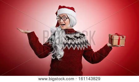 Funny woman in Santa hat with long white hair wearing an ugly Christmas sweater showing that she only got one present and her other hand is empty on red background.