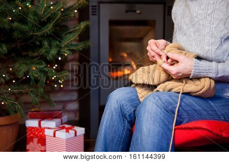 close up on old woman's hands sitting in red armchair and knitting - burning fireplace and Christmas tree with presents in the backgroung- cozy home concept