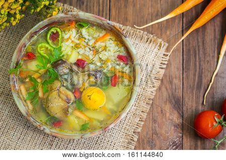 Rice soup with chicken navels and egg yolk. Wooden rustic background. Top view